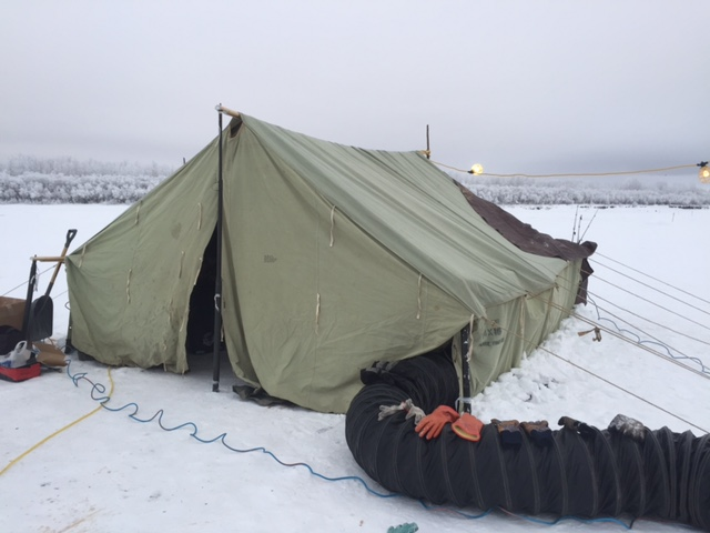 Wall tent heated with a space heater - a place for searchers to warm up and work on frozen equipment is very important when conducting a winter open water recovery. This is a well organized effort.