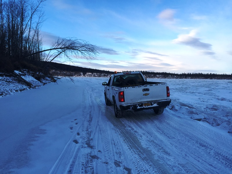 Truck trail is squeezed between the rough ice, half frozen overflow, and the cut bank just above Carl Morgan's fish camp